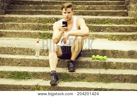 Athlete With Serious Face Sitting On Concrete Stairs With Phone