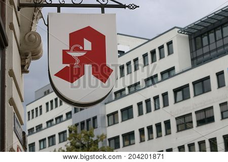 MAGDEBURG, GERMANY - September 14, 2017: Red pharmacy sign with snake on a house in Magdeburg.