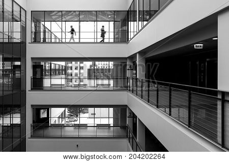 Modern public building interior with two figures walking in the background. High contrast black and white picture