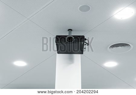 Multimedia projector hanging on the ceiling of modern conference room. Monochrome indoors picture