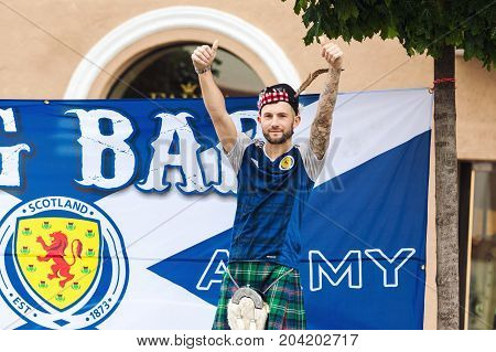 VILNIUS LITHUANIA - SEPTEMBER 1 2017: Young Scotland football team fan in national costume cheering and posing on the street in Vilnius Lithuania