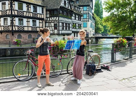 STRASBOURG FRANCE - JULY 03 2017: Two young adult girls playing flute in the background of fachwerk buildings in the old town of Strasbourg France