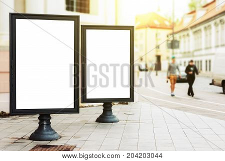 Two blank advertising billboards on the city street with pedestriants and sun glow