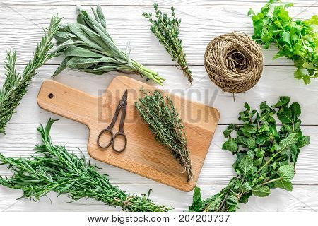 drying fresh herbs and greenary for spice home food on white wooden kitchen desk background top view pattern