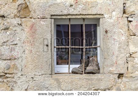 old house facade including a barred window and a pair of shoes