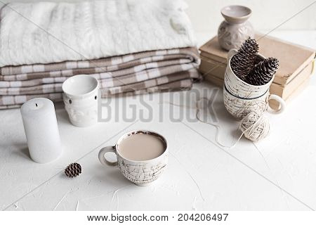 A cup of coffee with milk and a cosy wool plaid on the white concrete table in the morning. Winter or autumn season.