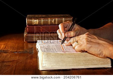 A man uses a pen to help him study an old and worn Holy Bible while other versions and/or translations of the bible are nearby on the wood table.