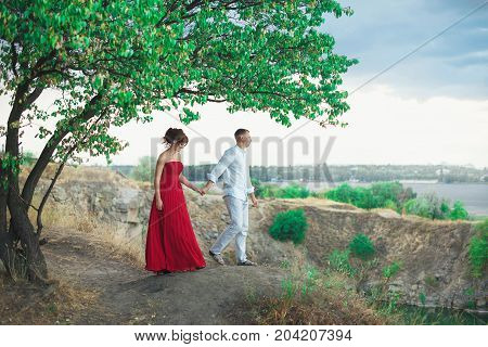Young Couple On Hill Under Big Tree At Sunset