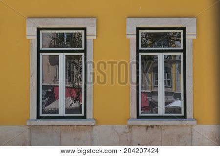 Two closed windows with a stone frame reflecting the city. Bright yellow facade. Lisbon Portugal.