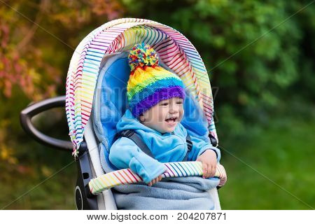 Baby Boy In Stroller In Autumn Park
