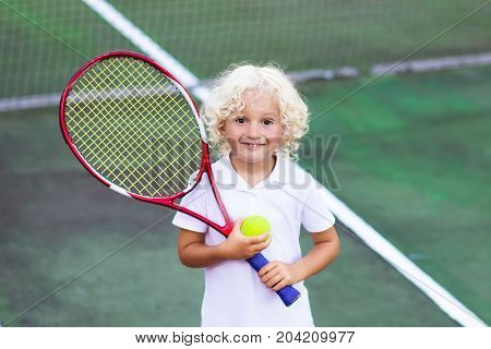 Child playing tennis on outdoor court. Little boy with tennis racket and ball in sport club. Active exercise for kids. Summer activities for children. Training for young kid. Child learning to play.