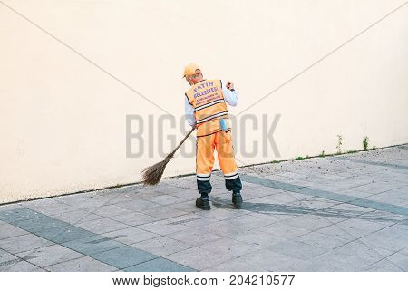 Janitor in bright orange uniform sweeping the tile on the street in Sultanahmet district in Istanbul, Turkey. Blank wall on the background.
