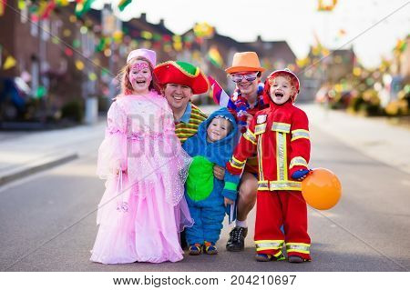 Kids And Parents On Halloween Trick Or Treat