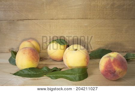 peaches on a brown background. Peaches with green leaves. view from above. peaches with green leaves.
