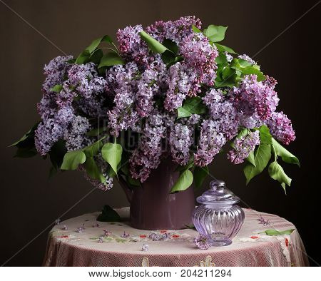 Bouquet of lilac in a jug on a round table with a retro tablecloth.
