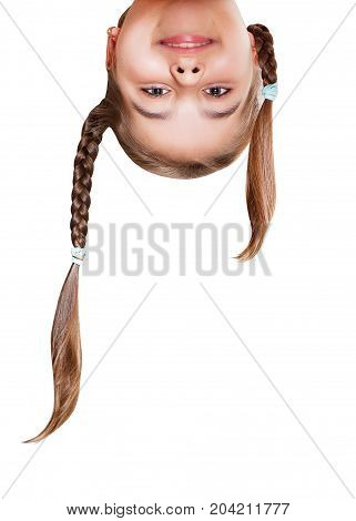 Funny girl with pigtails smiling looking upside down. Head portrait closeup.