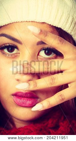 Closeup of young mulatto woman showing white painted nails. Mixed race girl in wintertime clothes studio shot