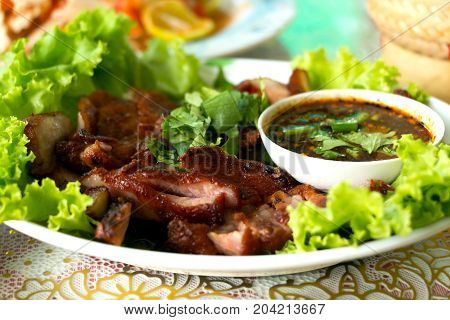 Charcoal-boiled pork neck served with spicy sauce and vegetable.