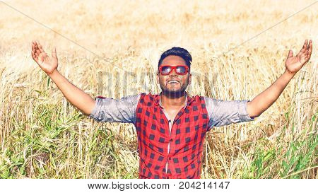 Young indian farmer raising arms in wheat field praising god for the harvest - African american man hands up at sky inside golden corn field on sunny summer day - Concept of successful hard farm work