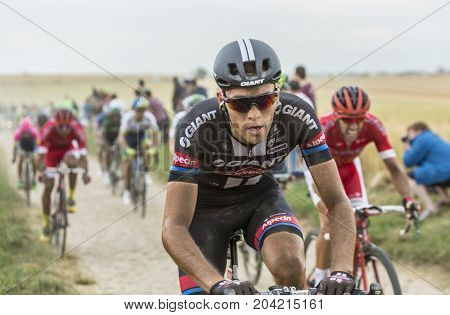 QuievyFrance - July 07 2015: Environmental portrait of the Austrian cyclist Georg Preidler of Giant-Alpecin Team inside the peloton riding on a cobblestoned road during the stage 4 of Le Tour de France 2015 in Quievy France on 07 July2015.