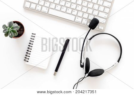 Workplace in call center. Headphones on keyboard and notebook on white background top view.