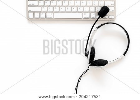 Workplace in call center. Headphones on keyboard on white background top view.