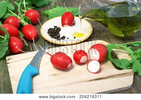 Radish on wood cutting board sliced for rustic snack with background red radishes and jug of olive oil dripping into saucer - Concept of eastern healthy vegetarian food