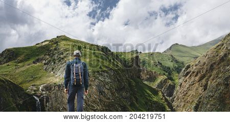 Young Traveler Man Standing On Top Of Cliff In Mountains And Enjoying View Of Nature Rear View