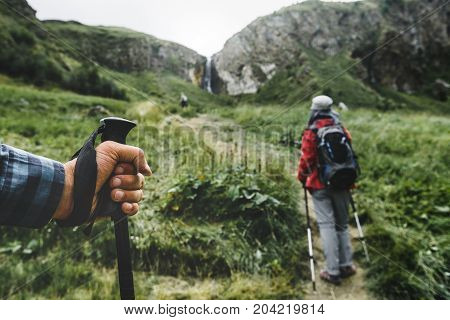 Hikers In The Mountains Trekking Pole In The Hand Of A Traveler Person Close-up. Travel Lifestyle Vacation Concept