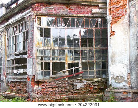 Old Ruined Abandoned House View From The Outside. Broken Glass In Window, Damaged Red Brick Wall