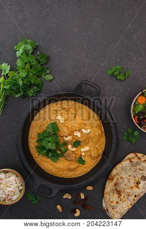 Lamb korma with cashew nuts, peshwari naan and Indian side dishes.  Top view, blank space
