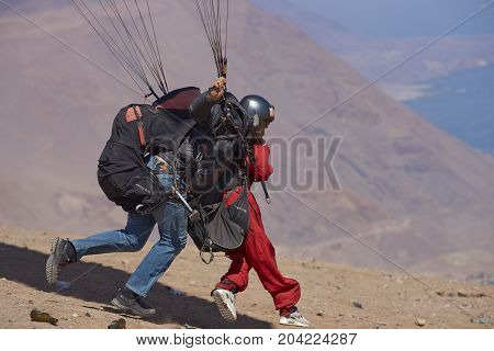 Iquique, Tarapaca Region, Chile - August 20, 2017: Tandem paragliding launch off a cliff above the coastal city of Iquique on the northern coast of Chile.