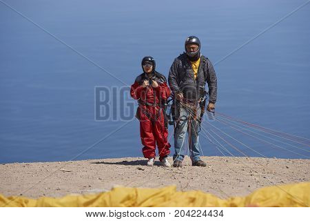 Iquique, Tarapaca Region, Chile - August 20, 2017: Tandem paraglider pilot and passenger prepare to launch over the coastal city of Iquique on the northern coast of Chile.