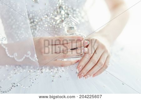 Perfume Bottle In The Hands Of The Bride. A Woman Is Preparing For Her Wedding. Bride In Elegant Wed