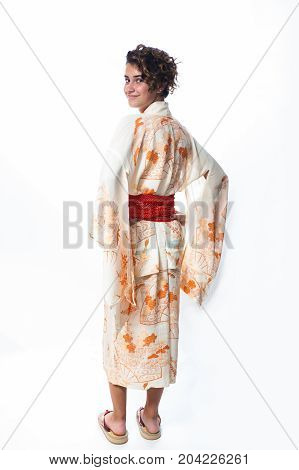 Teen age girl dressed in casual Japanese Yukata kimono looking over shoulder.