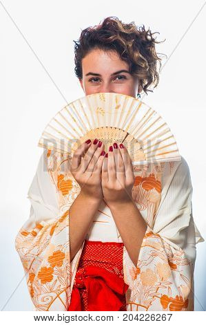 Teen age girl dressed in casual Japanese Yukata kimono holding paper fan over mouth.