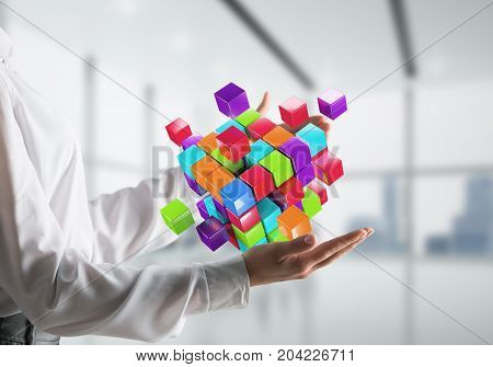Closeup shot of business woman hands holding multiple cubes of different colours in hands. Mixed media.