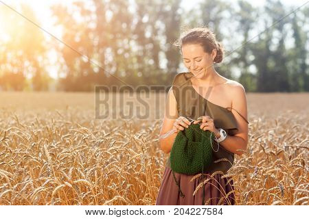 A dark-haired young woman in a green romantic top knits with knitting needles from a natural woolen thread of a green sweater in a wheat field on a summer day in the background a green forest