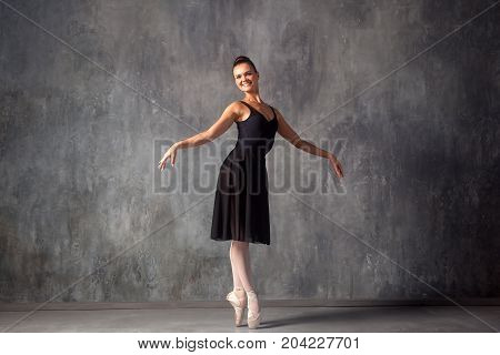 Young beautiful ballet dancer with gathered hair in a bun in a black dress pointe shoes smiling and beautifully dancing ballet in a dark dance studio