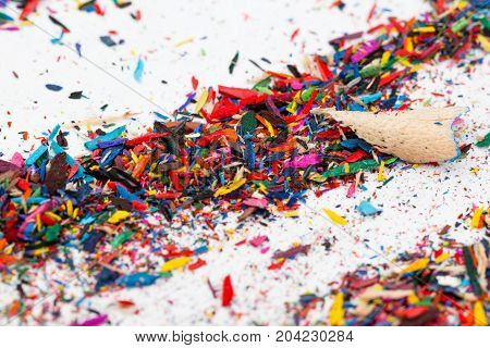 Small shavings from color pencils on grey background