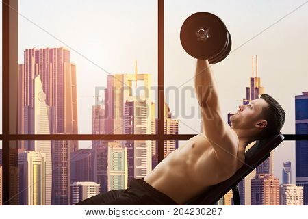 Young Muscular Man Working Out With Dumbbells In Front Of Window Overlooking The City