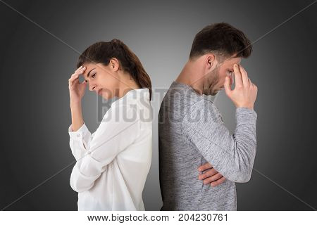 Young Frustrated Couple Standing Back To Back On Gray Background