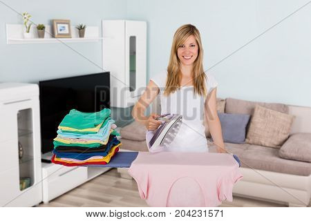 Happy Young Woman Ironing Clothes With Electric Iron In Living Room
