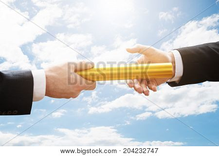Person Passing Golden Relay Baton To Another Person Against Cloudy Sky