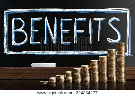 Social Security Benefits Drawn On Chalkboard Behind Coin Stacks