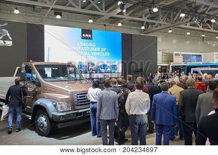 MOSCOW, SEP, 5, 2017: Presentation at GAZ group stand Russian cars vehicles manufacturer on Commercial Transport Exhibition ComTrans-2017. Peopel on exhibition stand among trucks, transport vehicles