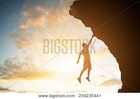 Silhouette Of A Man Climber Hanging Over The Rock With His Hand At Sunset