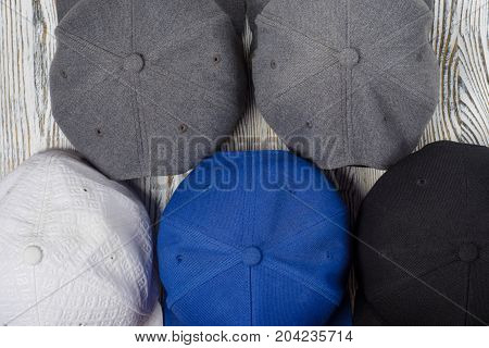 Snapback hats on white wooden background isolation
