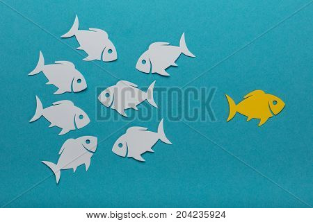 Yellow Fish Standing Out Of The Crowd White Paper Fishes Over Blue Background