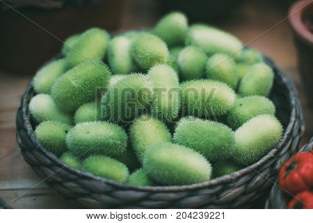 Braided basket staying on wooden table full of green and hairy tropical vegetable cucumis dipsaceus (also called Wild Cucumber or Hedgehog Gourd or Teasel Gourd) recently gathered poster